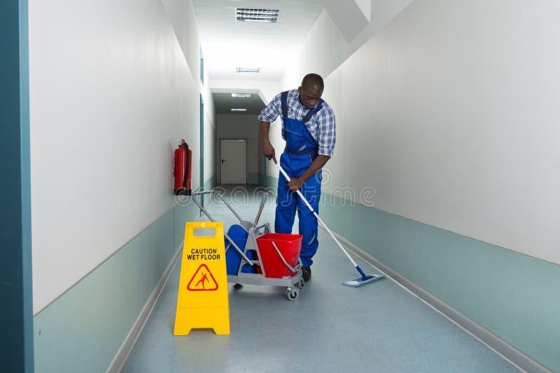Manlig dörrvakt Cleaning Floor royaltyfri foto