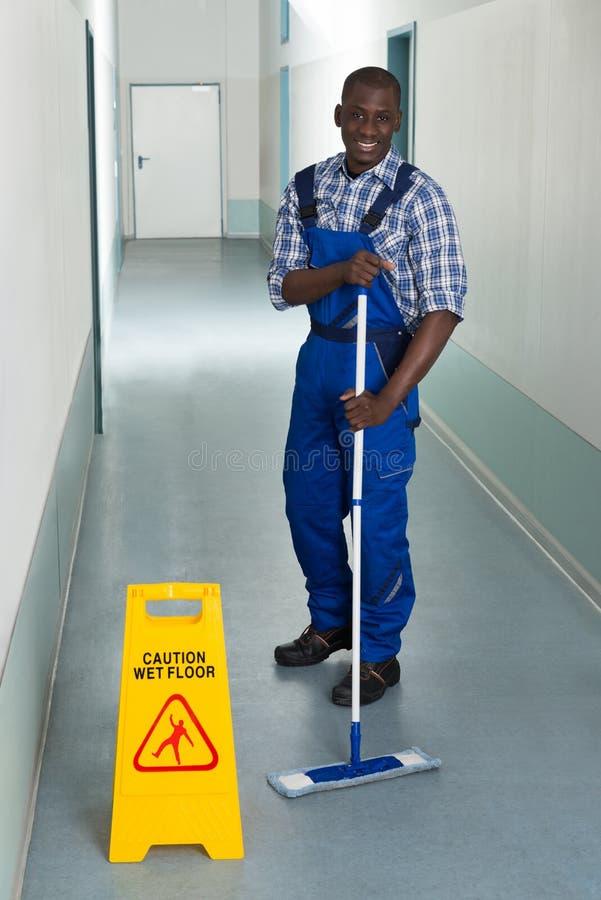 Manlig dörrvakt Mopping In Corridor arkivfoto