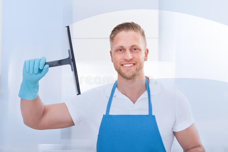 Manlig dörrvakt som använder en skrapa för att göra ren ett fönster arkivbild