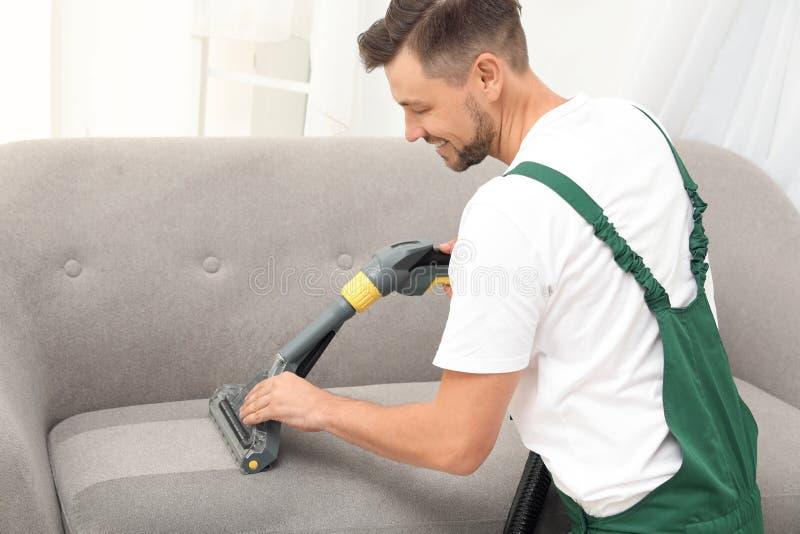 Manlig dörrvakt som tar bort smuts från soffan med rengöringsmedlet royaltyfria foton
