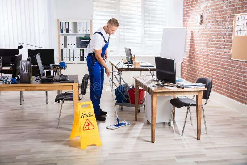 Manlig dörrvaktCleaning Floor With golvmopp arkivbilder