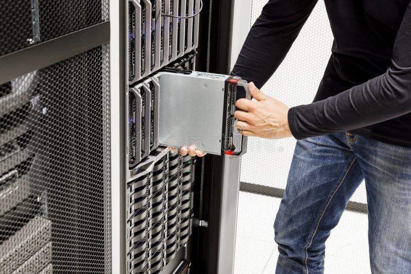 Manlig datortekniker Installing Blade Server i chassi arkivfoto