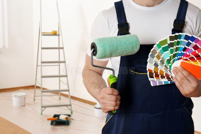 Manlig dekoratör med prövkopior för målarfärgrulle och för färgpalett i tomt rum Utrymme för text arkivfoton