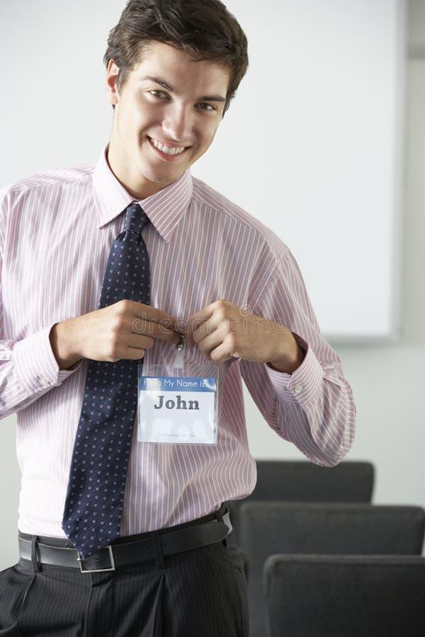 Manlig delegat som fäster det kända emblemet på konferensen royaltyfria bilder