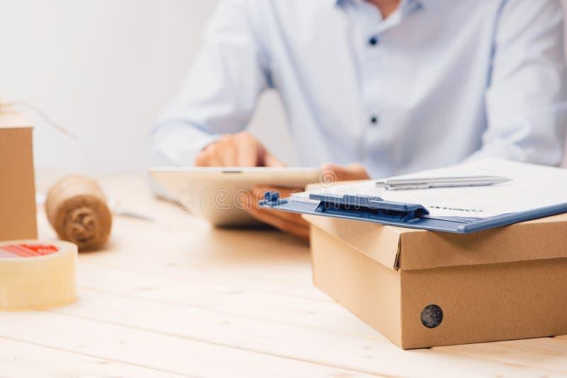 Manlig deliverer med minnestavlan på arbetsställe i stolpen - kontor arkivbilder