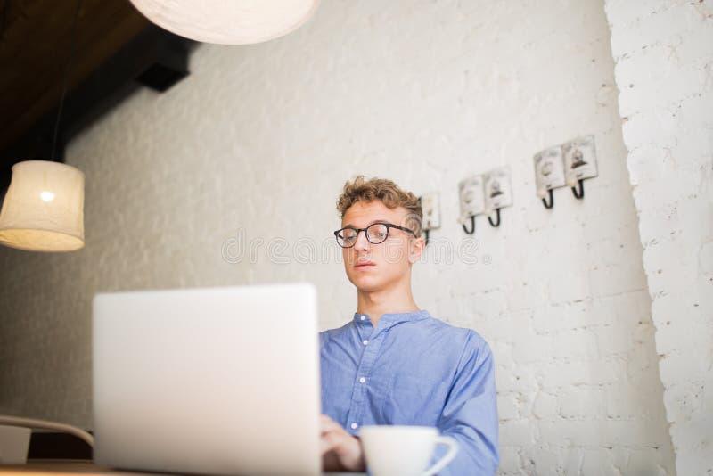 Manlig digital projektutveckling genom att använda bärbart netto-bok sammanträde med koppen kaffe i kafé arkivfoto