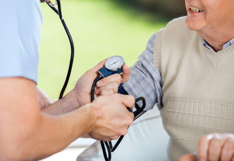 Manlig doktor Checking Blood Pressure av den höga mannen royaltyfri foto