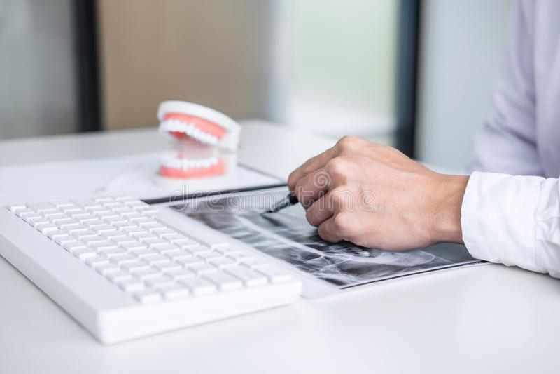 Manlig doktor eller tandl?kare som arbetar med den t?lmodiga den tandr?ntgenstr?lefilmen, modellen och utrustning som anv?nds i b arkivbilder