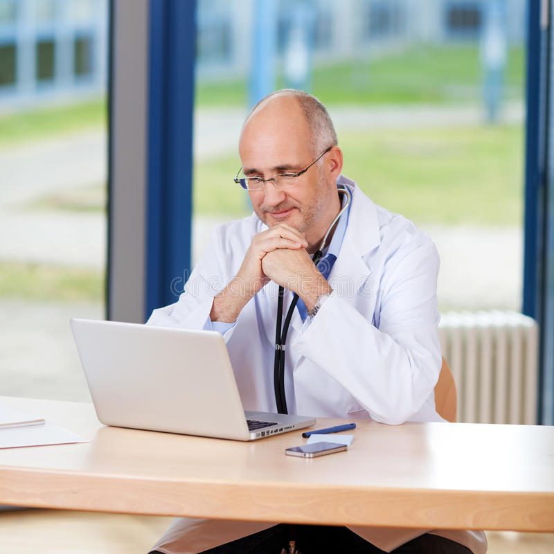 Manlig doktor With Hand On Chin And Laptop royaltyfria foton