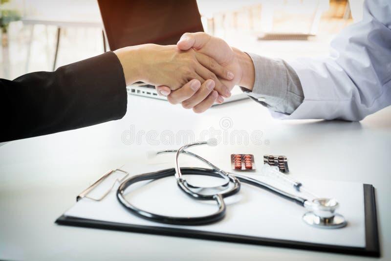 Manlig doktor i det vita laget som skakar handen till den kvinnliga kollegan fotografering för bildbyråer