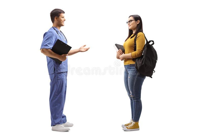 Manlig doktor i en blå likformig som talar till en kvinnlig student royaltyfri fotografi