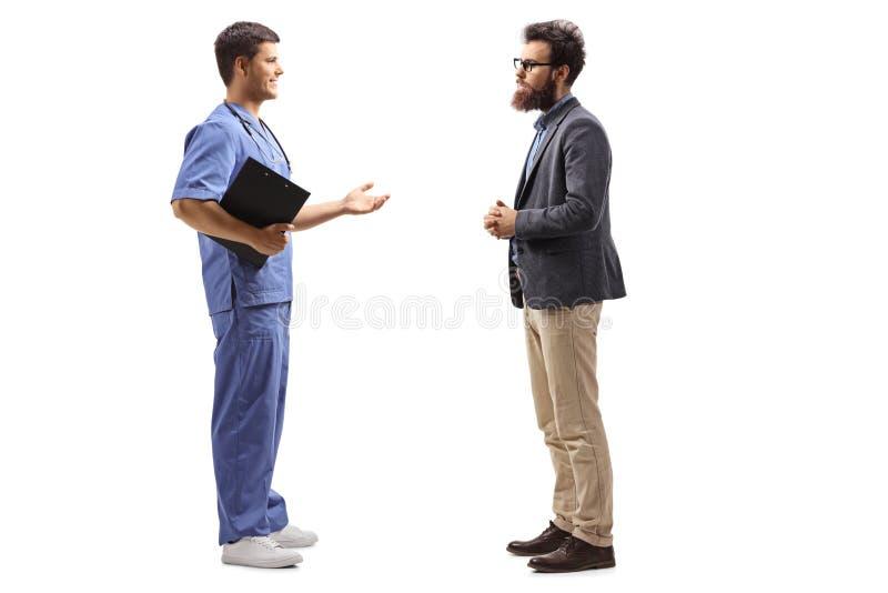 Manlig doktor i en blå likformig som talar till en skäggig man royaltyfria foton
