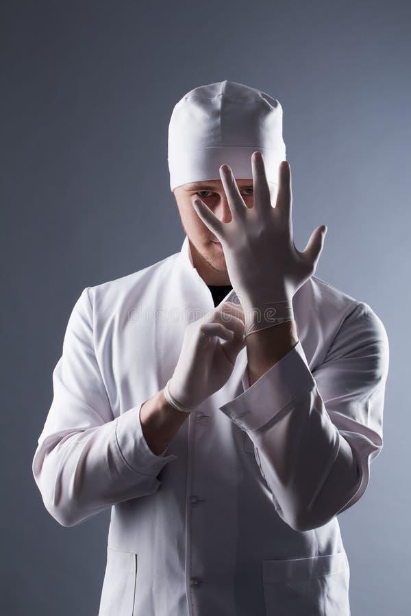 Manlig doktor i lock med rubber medicinska handskar för skäggkläder i cont royaltyfria foton