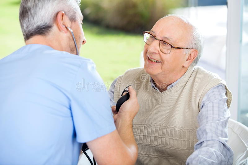 Manlig doktor Measuring Blood Pressure av den höga mannen royaltyfria bilder
