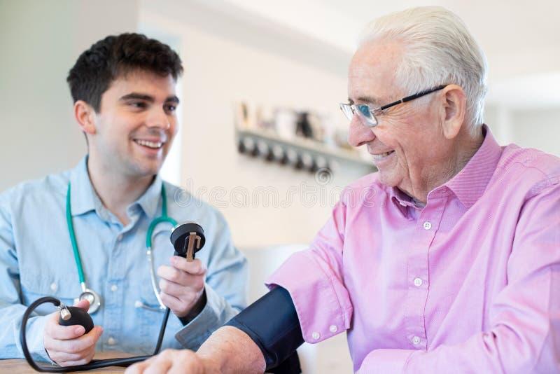 Manlig doktor Measuring Blood Pressure av den höga mannen hemma arkivbild