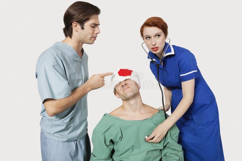 Manlig doktor med den kvinnliga sjuksköterskan som undersöker en sårad patient mot grå bakgrund arkivfoton
