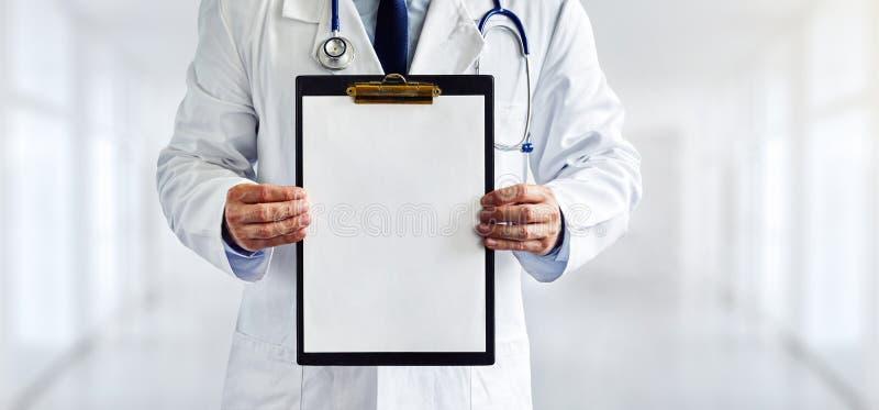Manlig doktor med den tomma skrivplattan i kliniken royaltyfri bild