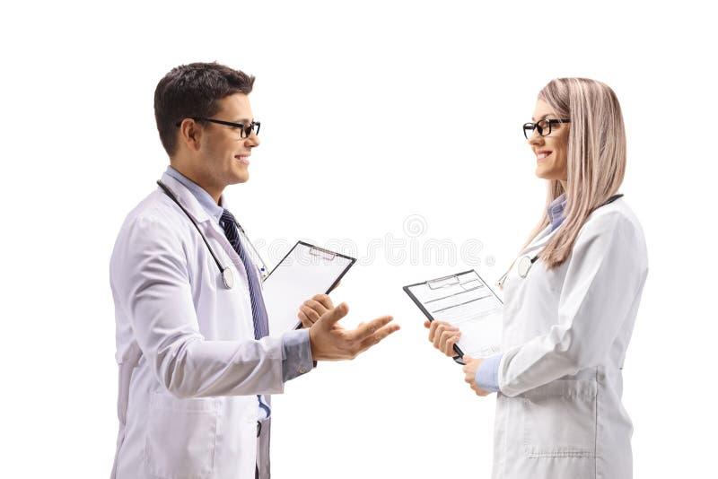 Manlig doktor med en skrivplatta som talar till en kvinnlig doktor royaltyfria foton