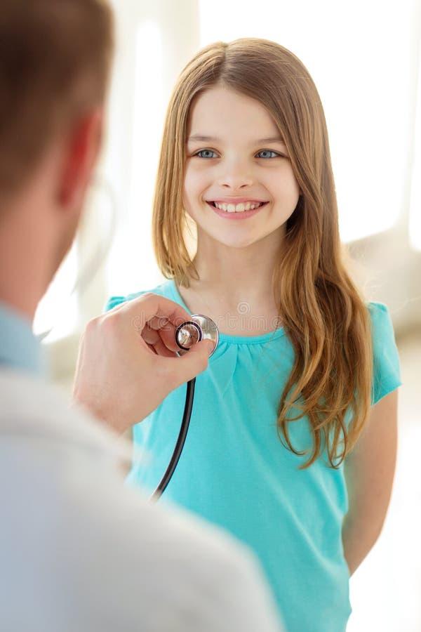 Manlig doktor med stetoskopet som lyssnar till barnet arkivbilder