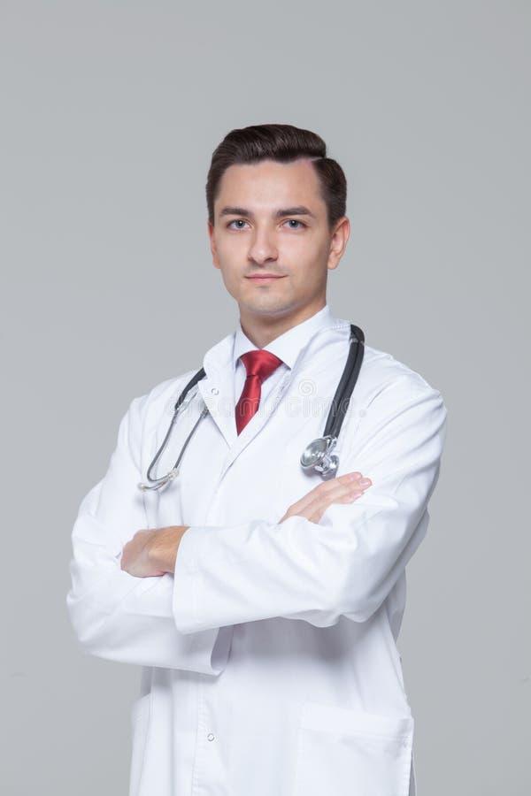 Manlig doktor med stetoskopet som st?r och ser kameran arkivbilder