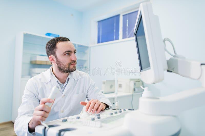 Manlig doktor med ultraljuds- utrustning under ultraljudläkarundersökning arkivbild