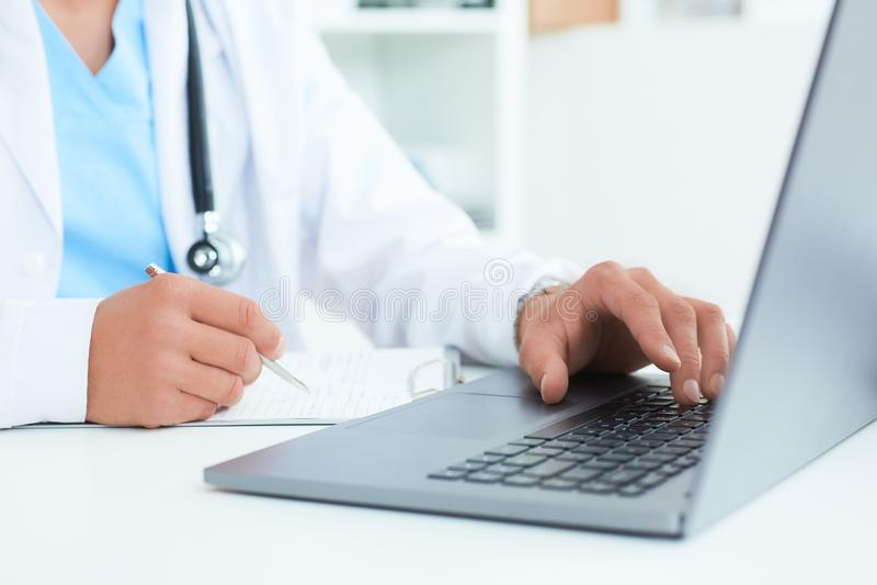 Manlig doktor, medicinare eller kirurg som använder bärbara datorn under konferensen Vård- kontroll med service för digitalt syst arkivbilder