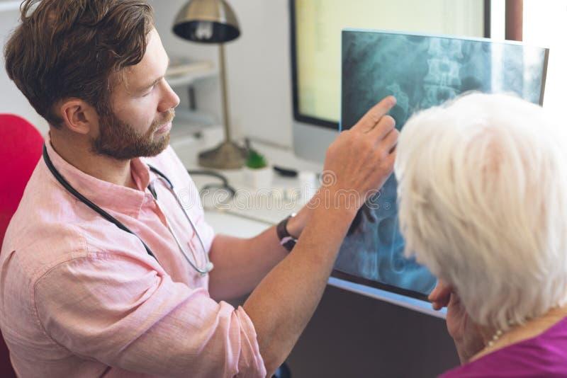 Manlig doktor och hög kvinnlig patient som diskuterar över x-stråle i klinik arkivbilder