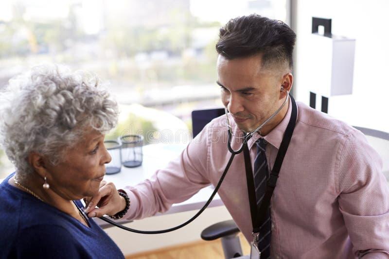 Manlig doktor In Office Listening till den höga kvinnliga patientbröstkorgen genom att använda stetoskopet royaltyfria bilder