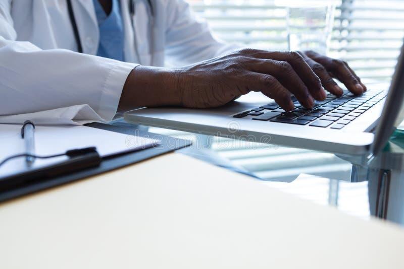 Manlig doktor som använder bärbara datorn på skrivbordet i sjukhuset arkivfoton
