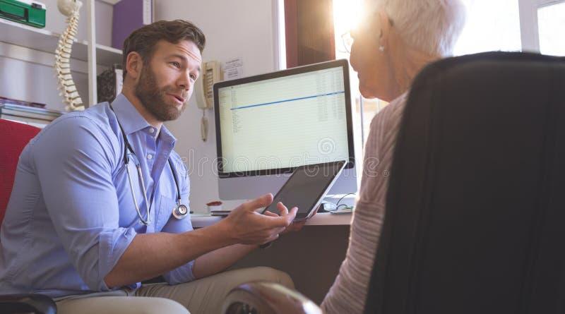Manlig doktor som använder den digitala minnestavlan, medan tala med den höga kvinnan i klinik royaltyfri bild