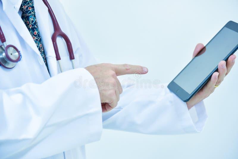 Manlig doktor som använder minnestavlan och bärbara datorn under konferensen, hälsa arkivfoto