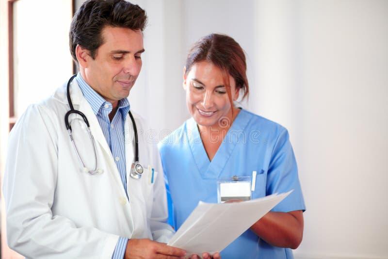 Manlig doktor som arbetar med den kvinnliga sjuksköterskan royaltyfria bilder