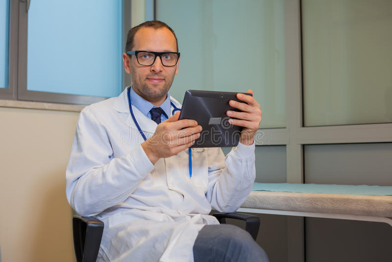 Manlig doktor som arbetar med en minnestavladator i hans kontor. Hospit royaltyfri bild