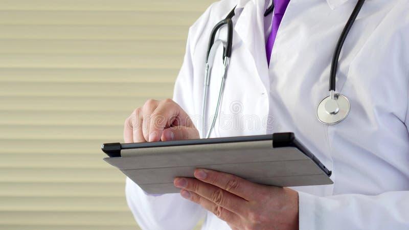 Manlig doktor som arbetar med en modern pekskärmminnestavladator royaltyfria foton