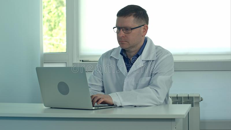 Manlig doktor som arbetar på bärbar datordatoren på det vita skrivbordet i sjukhus royaltyfria bilder