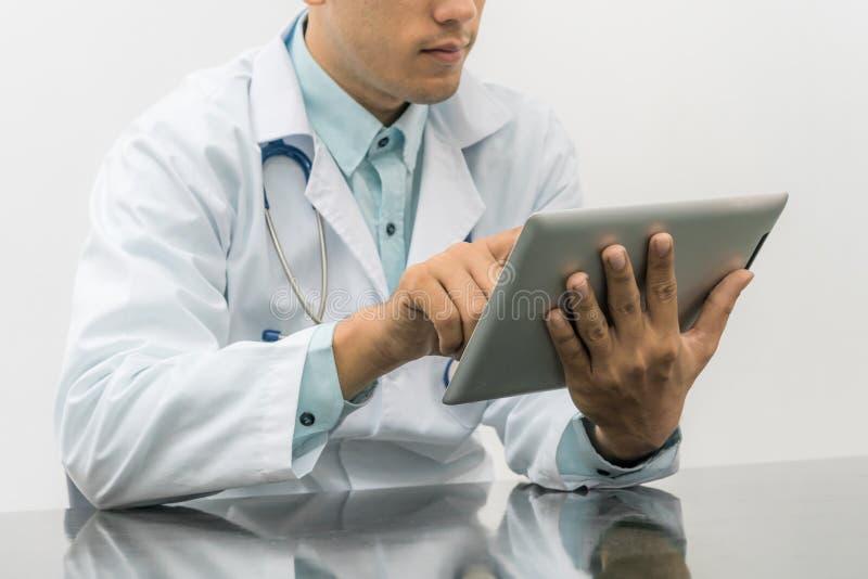 Manlig doktor som arbetar på datorminnestavlan royaltyfri bild