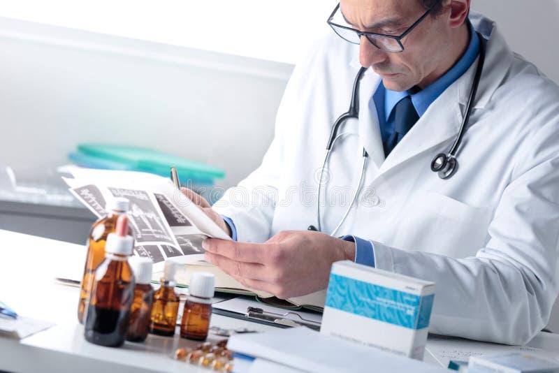 Manlig doktor som arbetar på hans kontorsskrivbord, undersökande läkarundersökningtekniker arkivbild