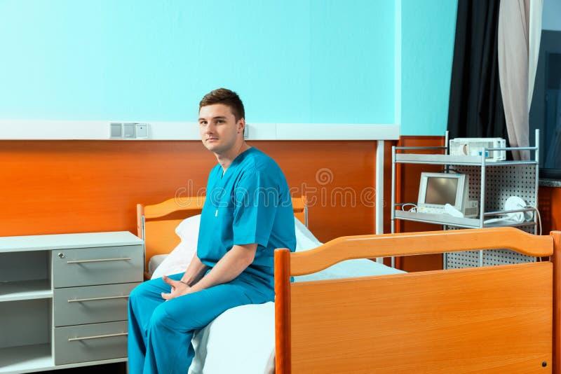 Manlig doktor som bär enhetligt sammanträde på en hans säng och vänta på arkivbild
