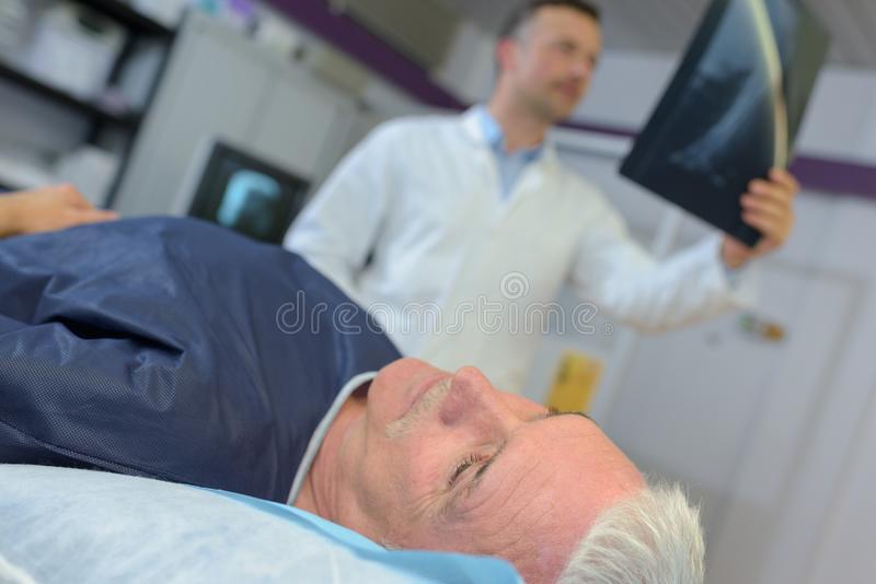 Manlig doktor som diskuterar röntgenstrålen med den höga mannen i sjukhus royaltyfri bild