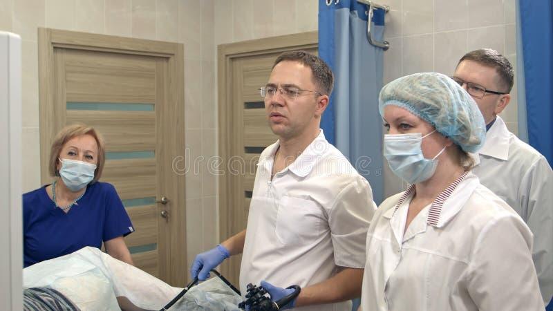 Manlig doktor som för endoscopic undersökning med hans lag fotografering för bildbyråer