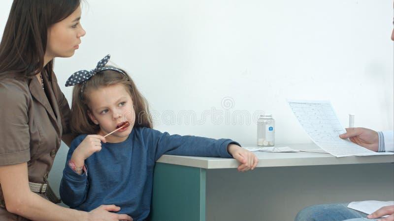 Manlig doktor som förklarar kardiogrammet till den allvarliga modern med lilla flickan på henne varvar arkivfoton