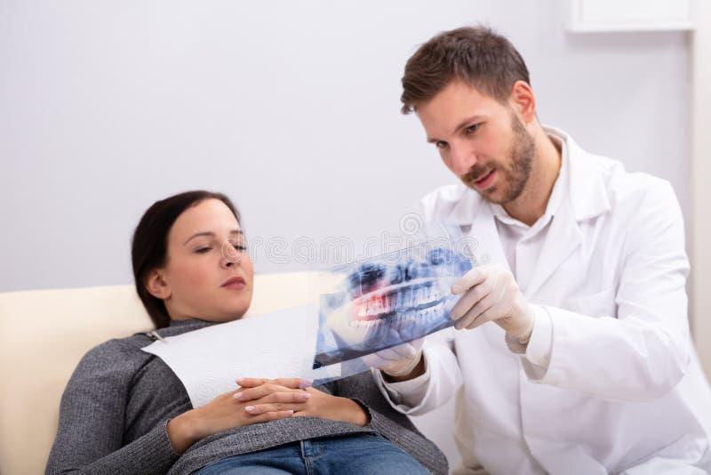 Manlig doktor som f?rklarar r?ntgenstr?len till patienten royaltyfri foto