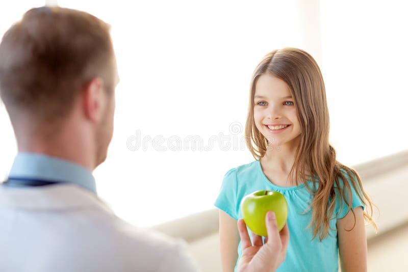 Manlig doktor som ger ett äpple till att le lilla flickan royaltyfri foto