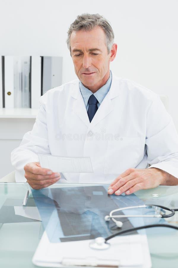 Manlig doktor som i regeringsställning läser en anmärkning på skrivbordet royaltyfri fotografi