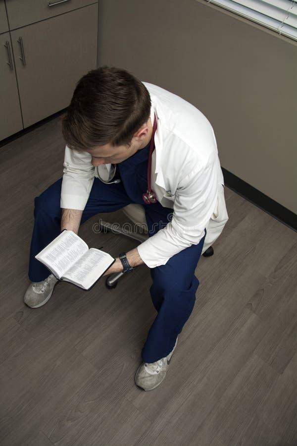 Manlig doktor som läser hans bibel royaltyfria bilder