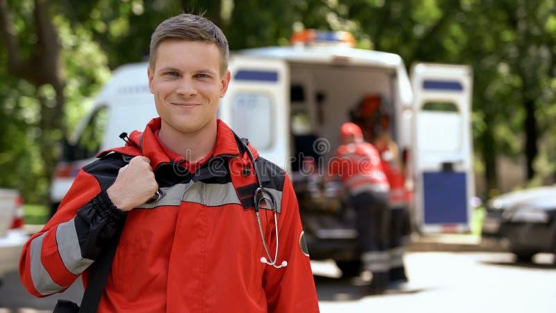 Manlig doktor som ler in i kameran, ambulansbesättningarbete som göras suddig på bakgrund arkivbild