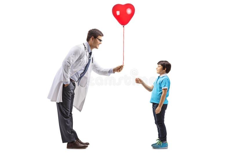 Manlig doktor som lite ger en röd hjärtaballong till pojken royaltyfri bild