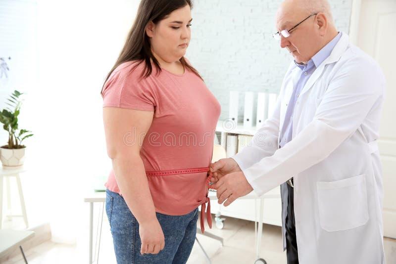 Manlig doktor som mäter midjan av den överviktiga kvinnan arkivfoton