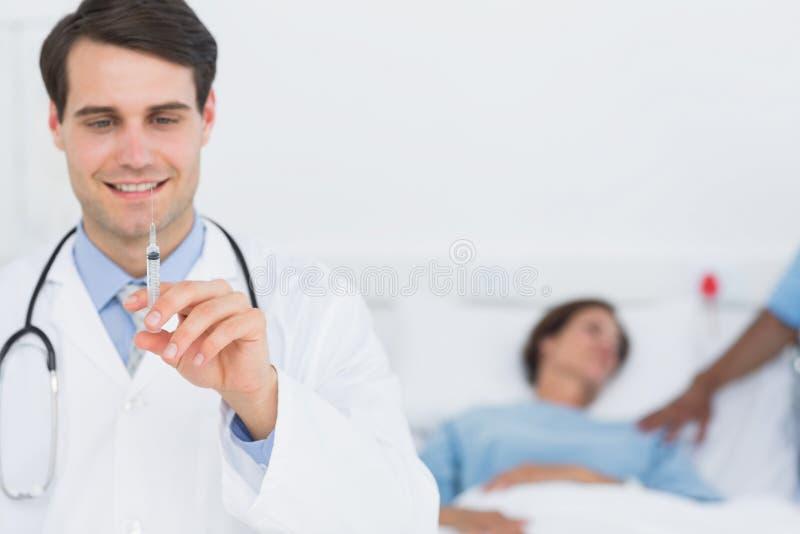 Manlig doktor som rymmer en injektion i sjukhuset royaltyfri foto