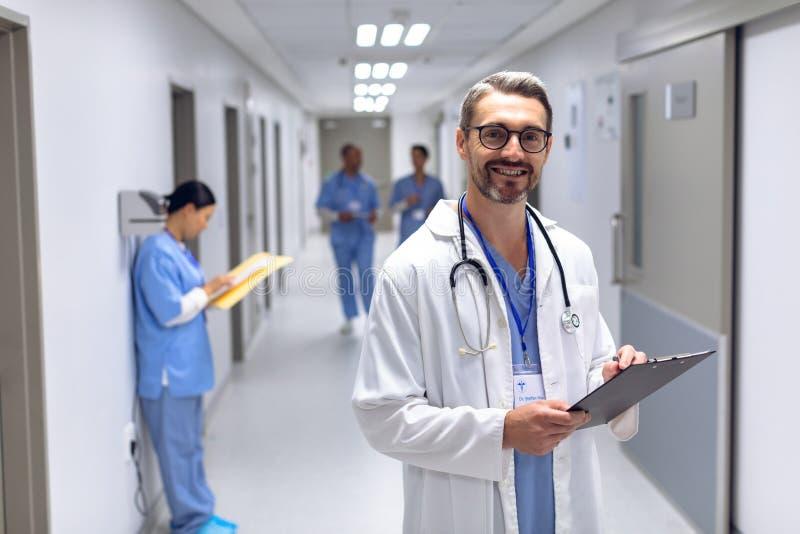Manlig doktor som ser kameran, medan skriva på skrivplattan i korridor på sjukhuset royaltyfria bilder